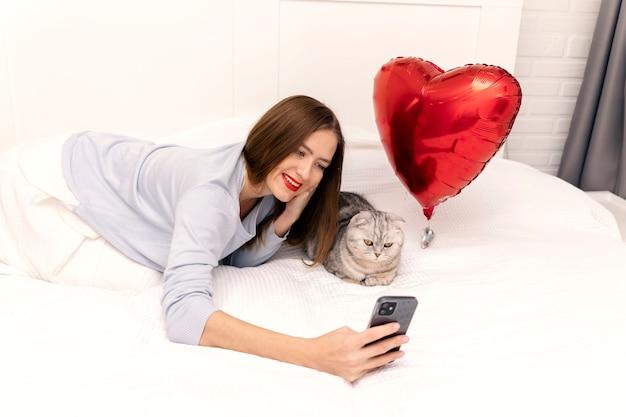Mujer joven hace un selfie con un gato en la cama. la habitación está decorada con corazones rojos. día de san valentín