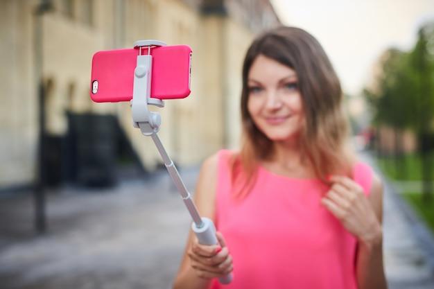 Mujer joven hace selfie con palo para teléfono móvil en la calle de la ciudad