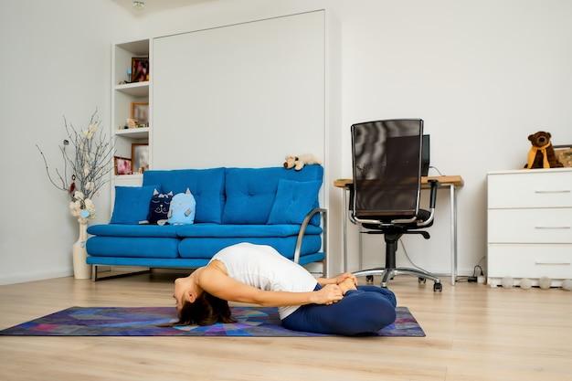 Mujer joven hace yoga en casa en pose de matsyasana