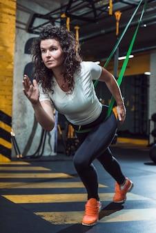 Mujer joven, hacer, entrenamiento, en, gimnasio