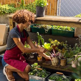 Mujer joven haciendo algo de jardinería en casa
