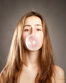 Mujer joven haciendo una burbuja de un chicle
