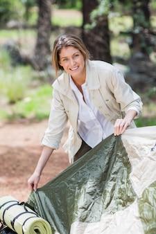 Mujer joven haciendo carpa mientras acampa