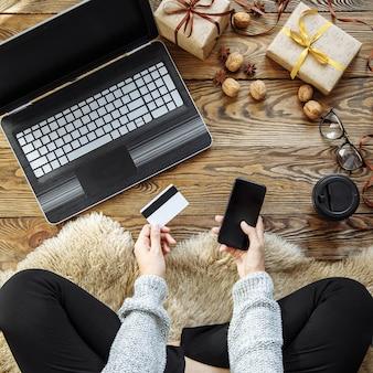 Mujer joven haciendo compras y comprando regalos usando laptop, smartphone y tarjetas de crédito