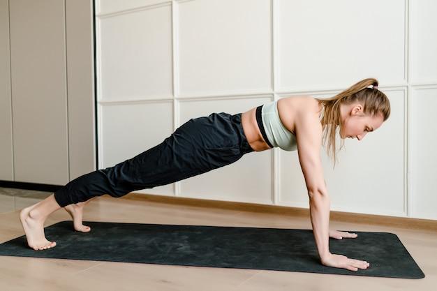 Mujer joven haciendo deporte en estera de yoga en casa