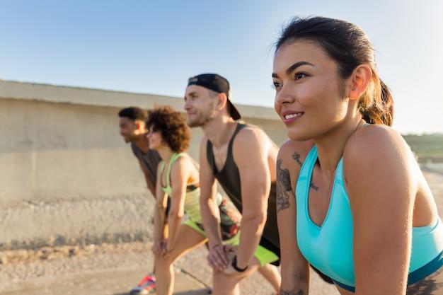 Mujer joven haciendo deporte con un grupo de amigos al aire libre