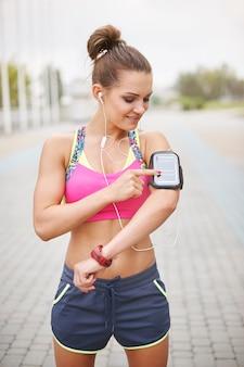 Mujer joven haciendo ejercicio al aire libre. lo que necesito mientras corro es buena música.