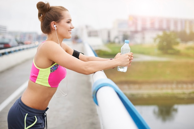 Mujer joven haciendo ejercicio al aire libre. sorbo de agua en el puente