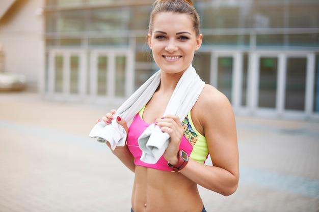 Mujer joven haciendo ejercicio al aire libre. la toalla es muy útil durante los ejercicios físicos.