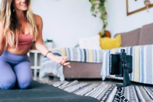 Mujer joven haciendo ejercicio en casa haciendo ejercicio y grabando en ella con teléfono celular para enseñar