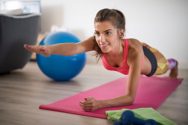 Mujer joven haciendo ejercicio en casa. satisfacción sacada del ejercicio en casa