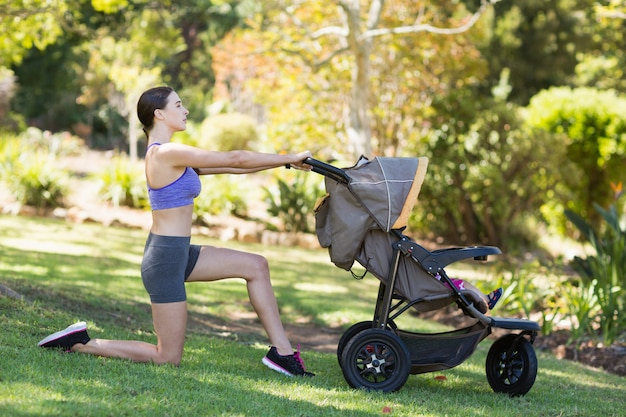 Mujer joven haciendo ejercicio con cochecito de bebé