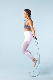 Mujer joven haciendo ejercicio con una cuerda para saltar