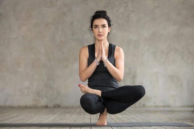 Mujer joven haciendo ejercicio de equilibrio de media loto del dedo del pie