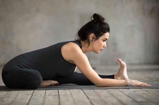 Mujer joven haciendo ejercicio de janu sirsasana.