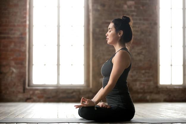 Mujer joven haciendo ejercicio padmasana