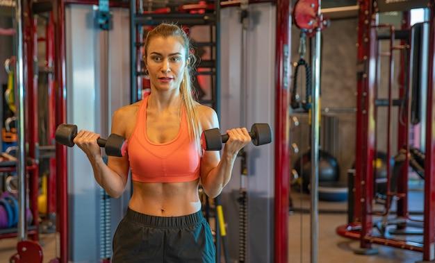 Mujer joven haciendo ejercicio con pesas para fortalecer los bíceps y los hombros en el gimnasio