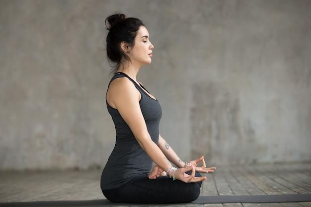 Mujer joven haciendo ejercicio sukhasana, vista lateral
