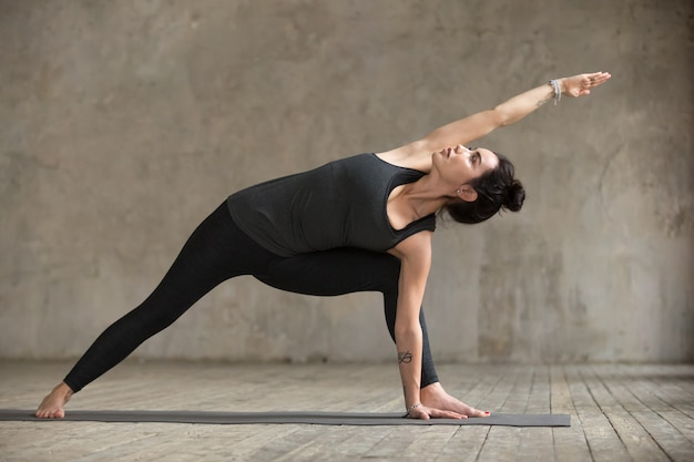 Mujer joven haciendo ejercicio utthita parsvakonasana