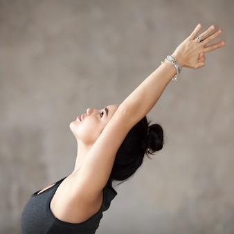 Mujer joven haciendo ejercicio de virabhadrasana 1.