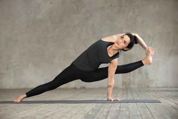 Mujer joven haciendo ejercicio de visvamitrasana.