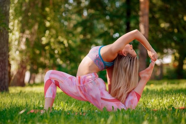 Mujer joven haciendo ejercicio de yoga al aire libre en el parque de verano