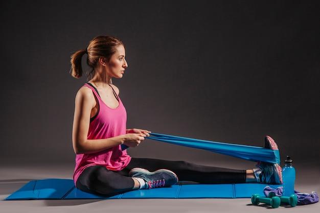 Mujer joven haciendo ejercicios con banda elástica