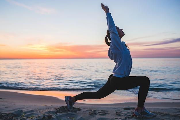 Mujer joven haciendo ejercicios deportivos en la playa del amanecer en la mañana