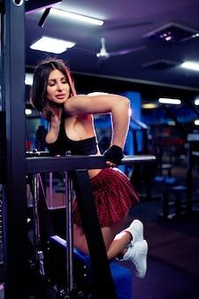 Mujer joven haciendo ejercicios para la espalda en la máquina de fitness en el gimnasio, vista desde la parte posterior. fitness, deporte, entrenamiento, concepto de personas