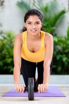 Mujer joven haciendo ejercicios de estiramiento en el interior