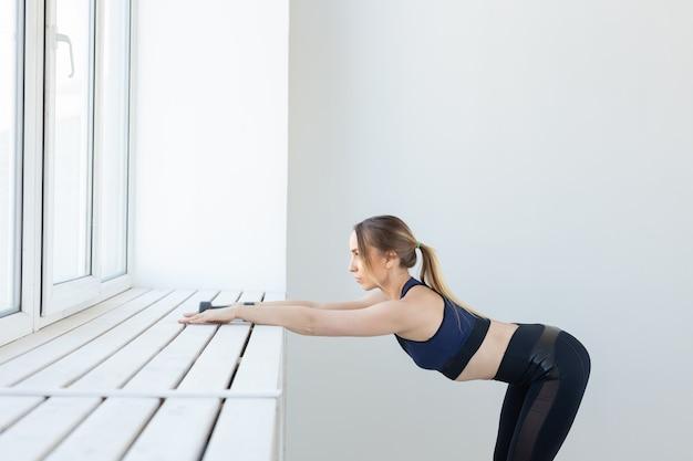 Mujer joven haciendo ejercicios de estiramiento junto a la ventana