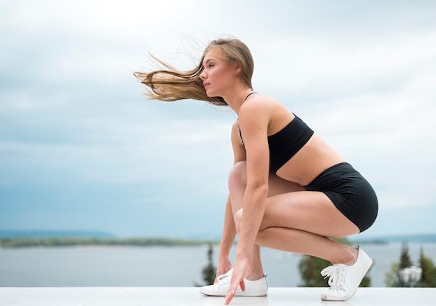 Mujer joven haciendo ejercicios de fitness tiro largo