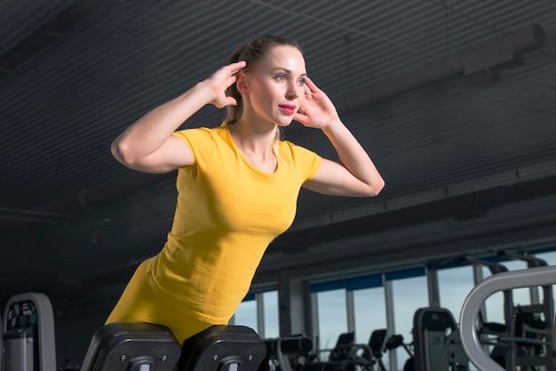 Mujer joven haciendo ejercicios en la máquina de abdominales en el gimnasio