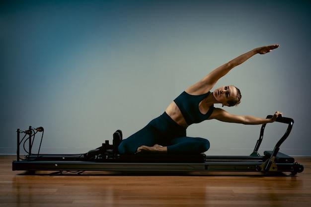 Mujer joven haciendo ejercicios de pilates con una cama reformadora