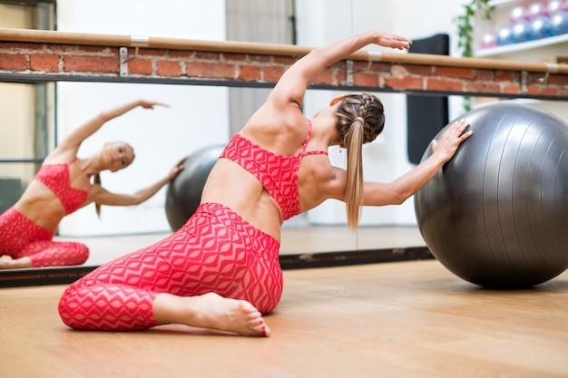 Mujer joven haciendo ejercicios de sirena de pilates