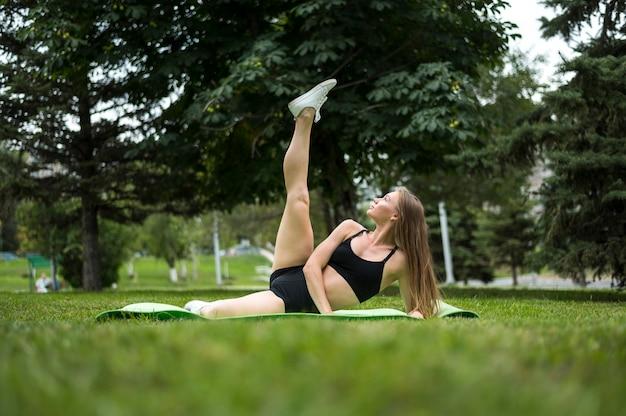 Mujer joven haciendo ejercicios tiro largo