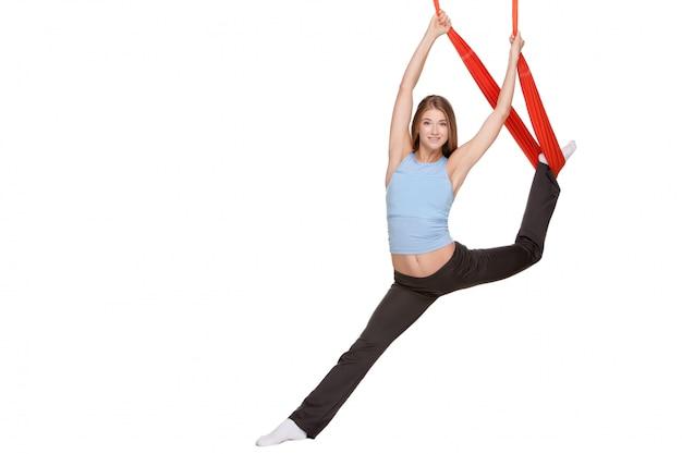 Mujer joven haciendo ejercicios de yoga antigravedad en estiramiento de hilo