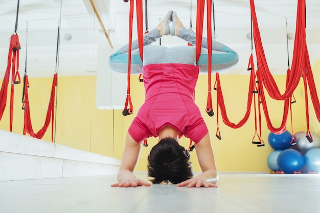 Mujer joven haciendo ejercicios de yoga antigravedad