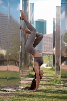 Mujer joven haciendo ejercicios de yoga, bella asana en las manos con la ciudad en el fondo.