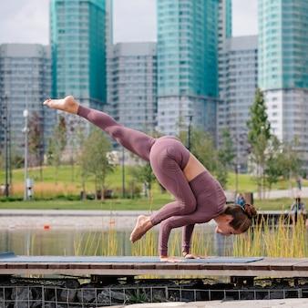 Mujer joven haciendo ejercicios de yoga, eka pada kaundiniasana con la ciudad en el fondo.