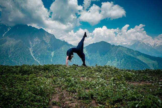 Mujer joven haciendo ejercicios de yoga en un entorno natural