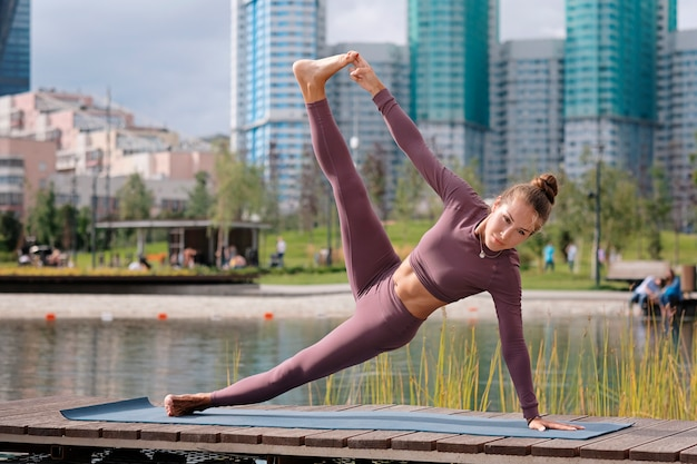 Mujer joven haciendo ejercicios de yoga, equilibrio hermoso plantean con la ciudad en el fondo.