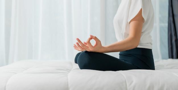 Mujer joven haciendo ejercicios de yoga en la sala de estar en casa.
