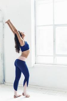 Mujer joven haciendo ejercicios de yoga