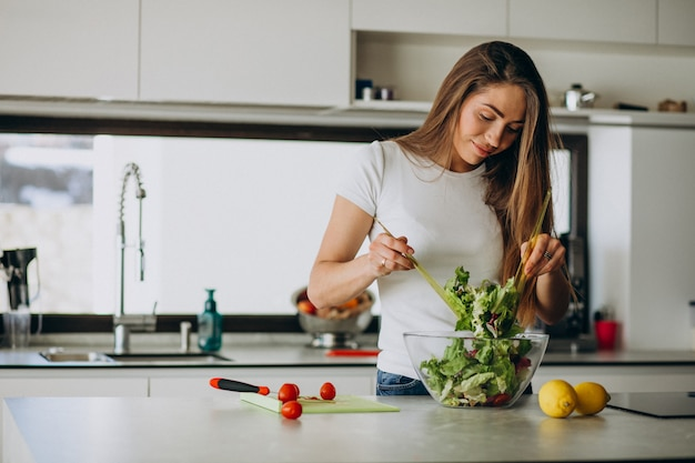 Mujer joven haciendo ensalada en la cocina