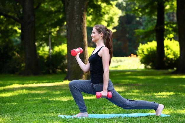 Mujer joven haciendo estocadas con pesas