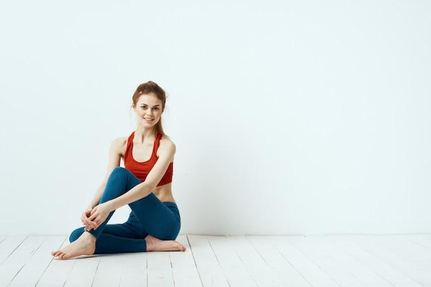 Mujer joven haciendo fitness en casa, entrenamiento y yoga.