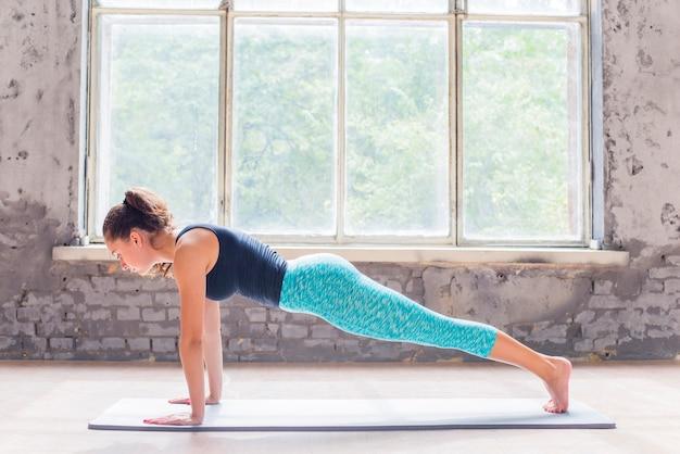 Mujer joven haciendo flexiones en la estera del ejercicio
