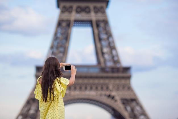 Mujer joven haciendo fotos por teléfono en la torre eiffel en parís