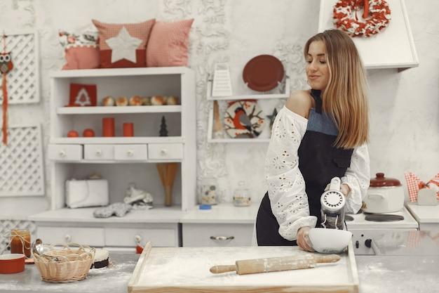 Mujer joven haciendo galletas en forma de navidad. salón decorado con adornos navideños al fondo. mujer con delantal.